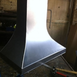 A finished steel canopy for a woodburning open fire ready to be hand scored and polished