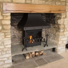 A re-modelled Cotswold fireplace with raised hearth including log store. Thermovent high performance wood burning open fire with stel canopy, hand