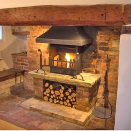 A re-modelled fireplace with raised hearth on brick plinths including log store. Thermovent high performance wood burning open fire with stel canopy,