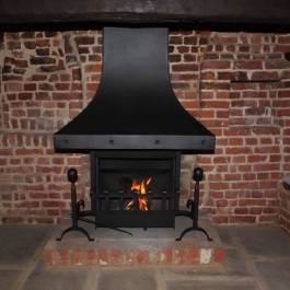 Anniversary Edition Thermovent high performance open fire featuring steel canopy with large studs added in this 350 year old Inglenook open fireplace.