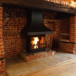 Anniversary Edition Thermovent high performance open fire installed in this large Inglenook open fireplace. The raised brick plint already in place.