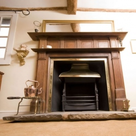 Classic stripped wood surround open fireplace with Georgian brass style canopy on Thermovent high performance convecting fire matches brass