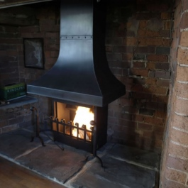 Large Inglenook fireplace with high performance Thermovent convecting open fire. Scroll top dog irons with swan neck ball top dog irons. Wood burning.