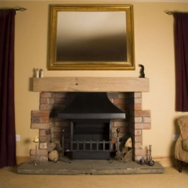 Medium size fireplace with themovent convecting open fire with traditional dog irons and grate front.