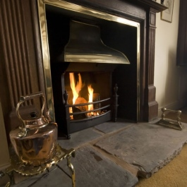 Natural wood surround open fireplace with Georgian brass style canopy on Thermovent high performance convecting open fire to match brass inner frame on the surround.
