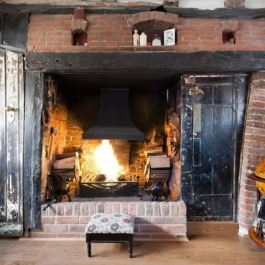 Preserved open fire with traditional canopy and bespoke grate used where chimney lined with large diameter liner. Storing logs this close not recommended.