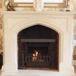 Stone fire surround open fireplace with Thermvoent convection fire featuring steel canopy with cast Fleur des Lis dog irons and scroll top grate front.