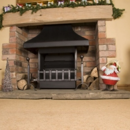 Thermovent convecting open fire in a medium size fireplace at Christmas time. Swan neck dog irons with ball tops and fish tail grate front.