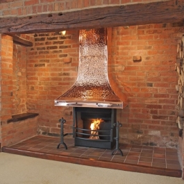 Thermovent high performance convecting open fire with large copper canopy and hand cast iron Fleur de lis dog irons