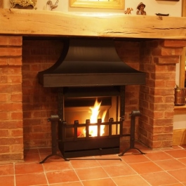 Therovent wood burning convection fire featuring clients own re-worked canopy and dog irons.