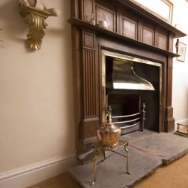 Antique stripped wood surround open fireplace with Georgian brass style canopy on Thermovent high performance convecting fire matches brass