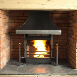 High polish steel canopy Thermovent convecting open fire with tall slender dog irons featuring ball tops. Square bar bow front grate.