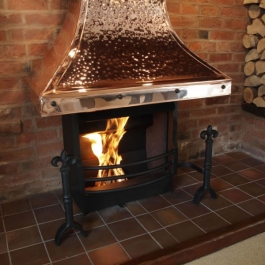 Inglenook open fireplace with large copper canopied Thermovent conecting open fire. Fluer des Lis dog irons with bow front grate.