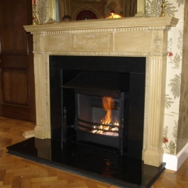 Polished granite & wood fire surround with steel canopied high performance woodburning open fire with built in flue baffle and convection system